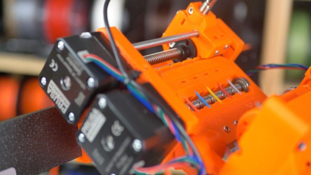 Подключение к 3D-принтеру специального устройства, называемого MMU (Multi Material Unit), позволяющего подавать несколько пластиков на стандартный директ-экструдер